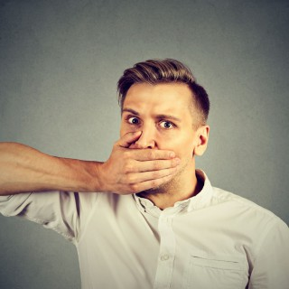 Scared young man covering mouth with hand isolated on gray wall background. Human emotion face expression, Image: 298457360, License: Royalty-free, Restrictions: , Model Release: yes, Credit line: Profimedia, Stock Budget