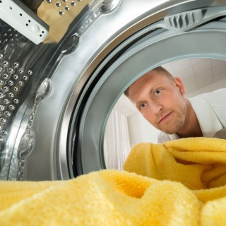 Young Man Putting Yellow Towel View From Inside The Washing Machine Appliance, Image: 259277410, License: Royalty-free, Restrictions: , Model Release: yes, Credit line: Profimedia, Stock Budget
